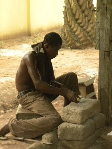 One of the workers making clay molds for the beads.